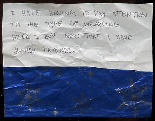 Zerknülltes Geschenkpapier, oben weiß mit Aufschrift: I hate having to pay attention to the type of wrapping paper I buy now that I have Jewish friends, unten blau mit silberglänzenden Schneeflocken
