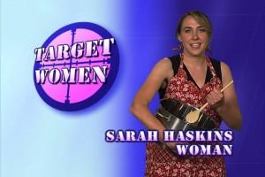 Screenshot aus Target Women: Links das rosa Fadenkreuz-Logo mit der Aufschrift -TARGET WOMEN- und rechts Sarah Haskins in einer roten Kittelschürze und mit Kochtops und Kochlöffel, darunter der Schrftzug - SARAH HASKINS - WOMAN