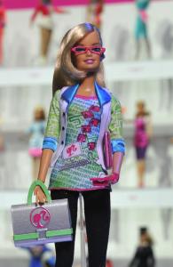 Career-Barbie als Computer-Spezialistin mit grün-blau-rosa Shirt im Binärcode und schwarzer Leggings, rosa Laptop unterm rechten Arm, sowie rosa Uhr und rosa Smartphone, außerdem einer grauen Laptoptasche in der linken Hand. Die Blondine trägt weiter eine rosa Brille und ein Bluetooth-Headset am rechten Ohr.