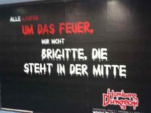 Schwarzes Plakat des Hamburg Dungeons mit der rot-weißen Aufschrift: ALLE LAUFEN UM DAS FEUER, NUR NICHT BRIGITTE, DIE STEHT IN DER MITTE.