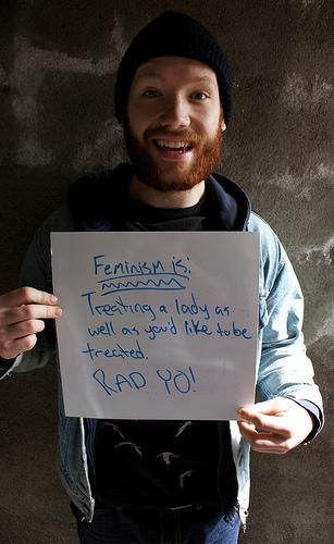 """Ein Mann mit rotem Bart und schwarzer Mütze hält ein weißes Plakat auf dem handgeschrieben """"Feminism is: Treating a lady as well as you'd like to be treated. RAD YO!"""" zu deutsch """"Feminismus: eine Frau so zu behandeln, wie du behandelt werden willst. Bombig, yo!"""" steht"""