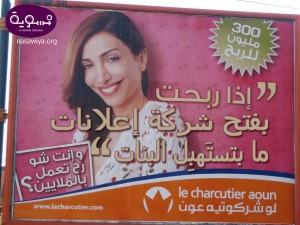 Rosa Werbeplakat mit einer lächelnden Frau und arabischer Schrift