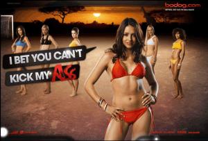 Sieben weiße Frauen stehen in bunten Bikinis auf einem Fußball-Sandplatz vor einem Sonnenuntergang. Im Vordergrund steht eine Brünette in rotem Bikini, die sagt: I bet you can't kick my ass