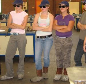 Schülerinnen stehen mit Schweißerbrillen und verschränkten Armen im Labor