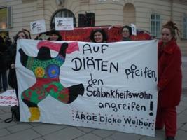 Plakat mit einer Nana und der schwarzen Aufschrift: Auf DIÄTEN pfeifen, den Schlankheitswahn angreifen! ARGE Dicke Weiber - Hinter und neben dem Plakat stehen Frauen der ARGE