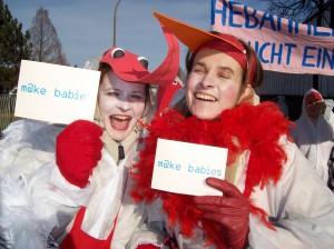 """Hebammen in weiß-roten Storchenkostümen, Schilder mit der Aufschrift """"m@ke babies"""" haltend"""