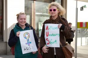 Zwei junge Frauen die Plakate vor dem Körper halten. Das eine mit dem Venusspiegel, darunter die Schrift: AUS! Das andere mit der Aufschrift: Aktion Umsetzung. Sofort.