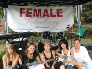 Die 5 Schülerinnen von Female Solution sitzen auf einer Bühne, mit Instrumenten auf dem Schoß und im Hintergrund. Hinter ihnen hängt ein weißes Banner mit der Aufschrift: FEMALE Solution Die Frauenband!