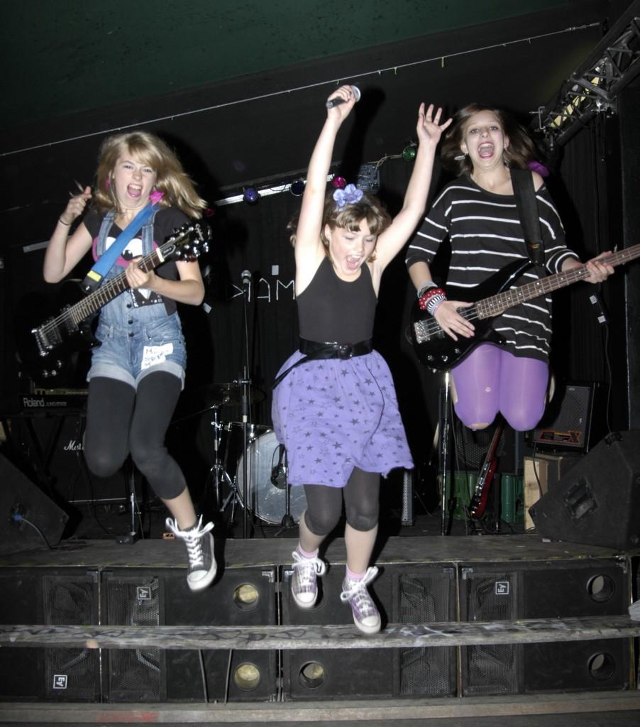 3 Mädchen mit Instrumenten springen auf einer Bühne in die Luft