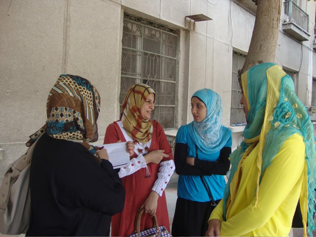 YMS-Teilnehmerin Huda Jafar mit Schreibblock interviewt drei junge Frauen, bunt gekleidet in rot, blau und gelb vor der ägyptischen Zentralverwaltung