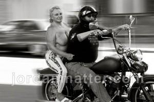 Schwarz weißes Foto eines älteren Pärchens auf einem Motorrad. Er lenkt mit schwarzem Helm und Sonnenbrille, sie sitzt oben ohne dahinter.