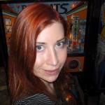 Eine Frau mit schulterlangen roten Haaren vor einem Glücksspielautomaten (Meow Meow Meow ramp)