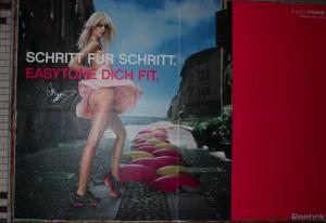 Eine weiße, blonde, schlanke Frau steht im hochfliegenden rosa Kleidchen in sexualisierter Pose auf der Straße, vor ihr kommen pinke und gelbe Gymnastikbälle aus der Straße.