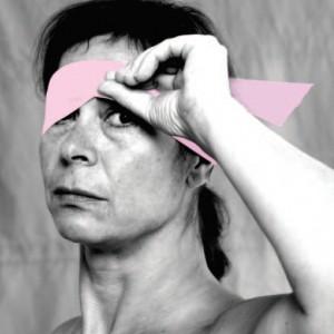Schwarzweißporträt einer ernst blickenden Frau, die sich eine rosafarben kolorierte Augenbinde abnimmt, so dass ein Auge bereits zu sehen ist