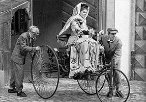 Bertha Benz, eine weiße Frau mit hellen Gewändern sitzt im Benz Patentwagen, zwei Männer schieben die Hinterräder. Ca. 1880.