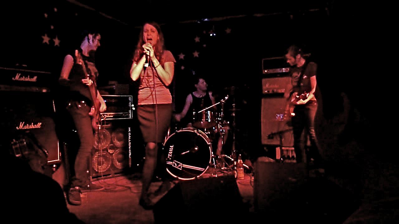 Vier junge Frauen an ihren Instrumenten (Schlagzeug, Gitarre, Bass, Gesang) auf einer kleinen, dunklen Bühne.