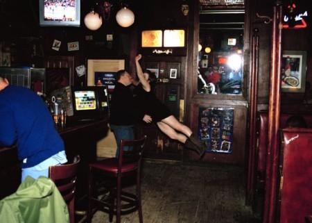 Eine weiße Frau in schwarzem Kleid springt auf einen stämmigen weißen Mann zu, der seine Hände nach ihr ausstreckt. Im Hintergrund des Pubs sieht man einen Spiegel, in dem das Blitzlicht reflektiert wird.