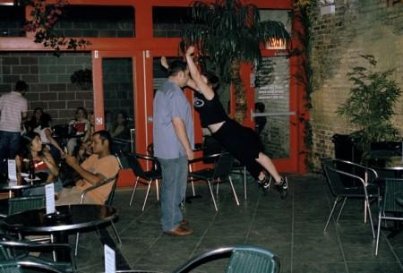 Eine weiße Frau in schwarzem Shirt und Rock springt auf einen stämmigen weißen Mann zu, der bewegungslos in einem Diner steht.
