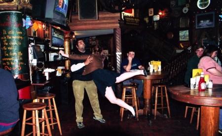 In einem Pub: Eine weiße Frau in schwarzem Kleid  und brauner Lederjacke springt auf einen stämmigen Latino-Mann zu, der sie gerade auffängt. Dahinter sitzt ein weißer Mann und schaut skeptisch.