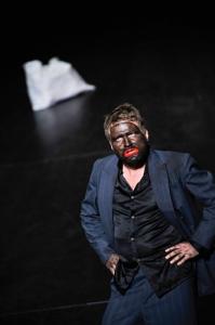 Ein weißer Mann mit dunkelblauem Hend und blauen Jacket steht alleine auf einer Bühne, sein Gesicht ist schwarz angemalt, mit einem riesigen roten Mund