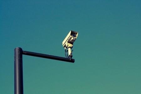 Blauer Himmel, davor eine weiße Kamera an einem schwarzen Mast