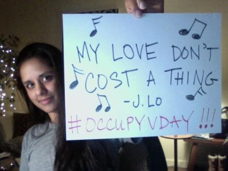 Eine junge Frau mit schwarzen Haaren hält ein weißes Schild in die Kamera, neben vielen Noten steht: MY LOVE DON'T COST A THING - J.LO #OCCUPYVDY (Meine Liebe kostet nichts)