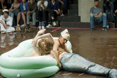 Szenenbild der Mermaid Show von Ann Liv Young: Ein weißer Mann in einem grünen Planschbecken zieht eine Meerjungfrau in dieses.