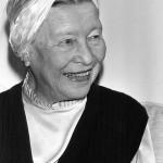 Eine weiße, ältere Frau mit einem weißen Band in den Haaren und einem schwarz-weißen Oberteil