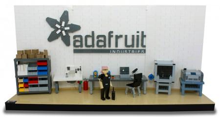 Blick auf den Vorschlag für den Adafruit Werkraum: Mit Regal, Nähmaschine, Schreibtisch mit Laptop und Lötkolben, Lasercutter und Bestückungsautomat. Sowie eine Legofigur mit pinken Haaren und einer schwarzen Katze.