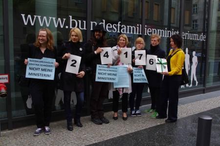 Sieben Personen stehen vor dem Frauenministerium, sie halten Plakate mit den Ziffern 24176 und dem Stapel Unterzeichnungen hoch.