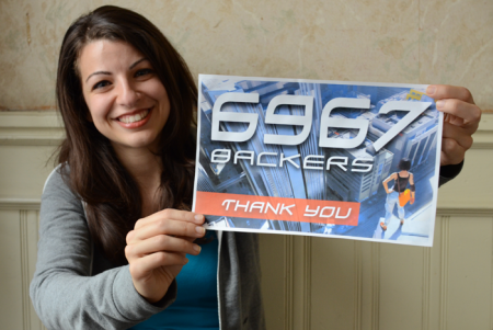 Anita Sarkeesian mit einem Schild 6967 Backers – Thank you!
