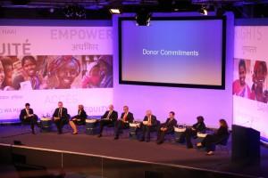 """Vertreter_innen verschiedener europäischer Länder und Süd-Koreas sitzen auf einer Bühne, dahinter auf einer Leinwand steht """"Donor Commitments"""""""