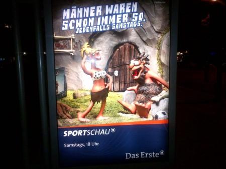 Werbeplakat der Sportschau. Ein Neanderthalermann schaut einer Neanderthalerfrau auf die Brust, die mit einem BH mit Fußballmotiv bedeckt ist