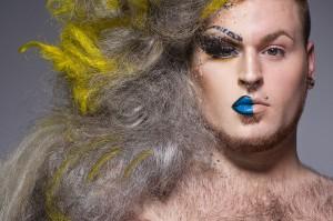 Ein weißer Mann, dessen linke Gesichtshälfte u.a. mit blauem Lippenstift geschminkt ist, er trägt wallende graue Haare mit gelben Akzenten