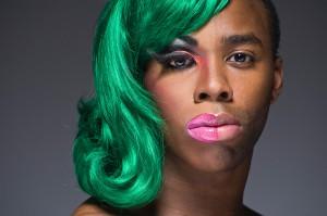 Ein schwarzer Mann, dessen linke Gesichtshälfte u.a. mit pinkem Lipgloss geschminkt ist, er trägt glatte grüne Haare