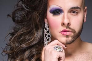 Ein weißer Mann mit Bart auf der rechten Seite, seine linke Gesichtshälfte ist u.a. mit lila Lidschatten geschminkt; er trägt dunkelbraune Locken und einen großen silbernen Ohrring