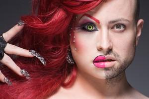 Ein weißer Mann, dessen linke Gesichtshälfte u.a. mit rosa Lippen geschminkt ist, er trägt eine gelbe Kontaktlinse und rote Locken, die langen Nägel sind mit Glitzersteinen besetzt