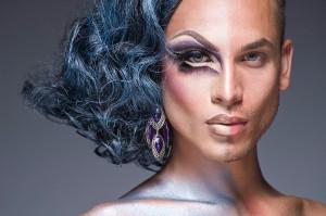 Ein weißer Mann, dessen linke Gesichtshälfte u.a. mit lila Lidschatten geschminkt ist sowie blauen mittellangen Locken