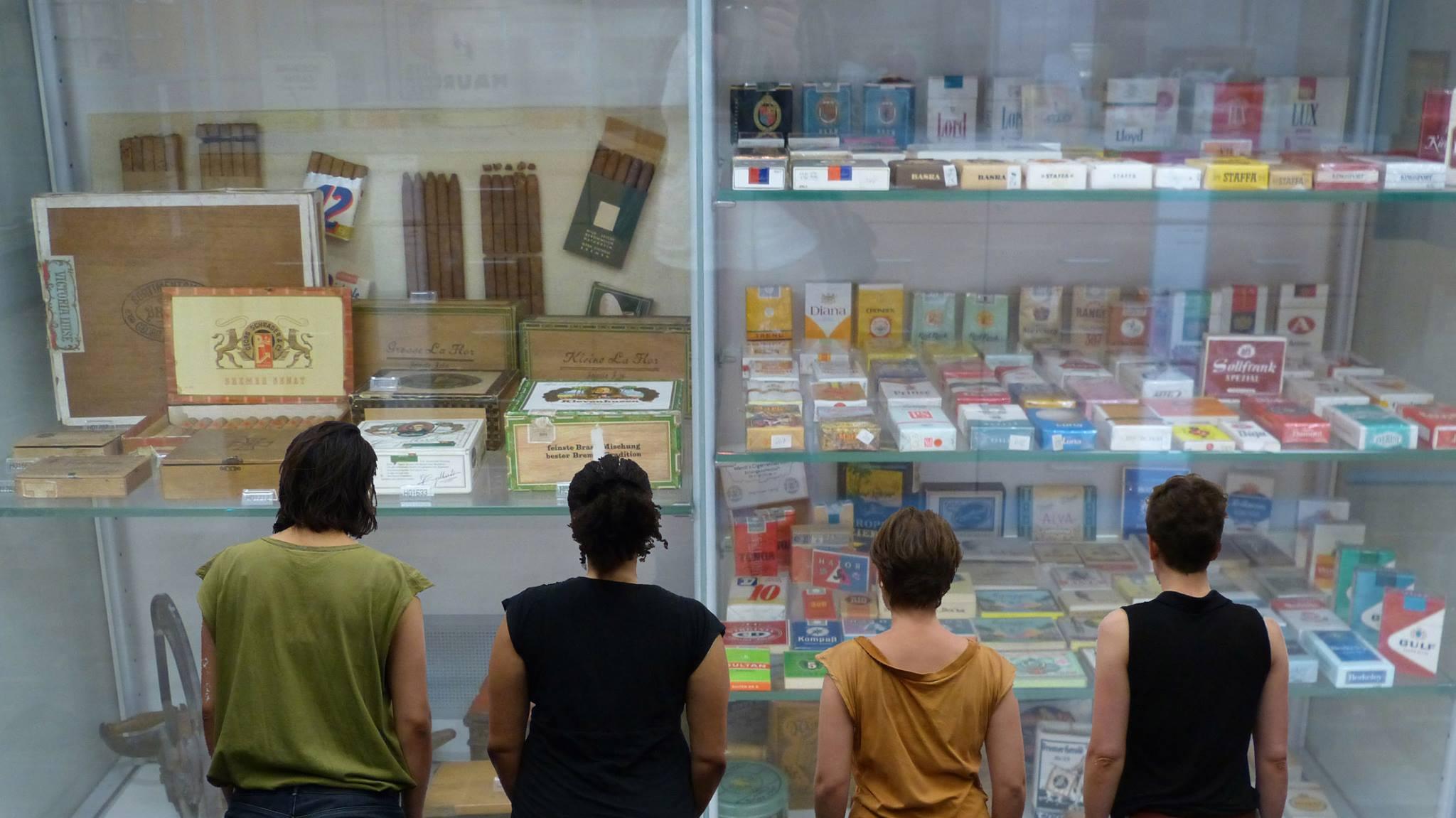 """Veranstaltungsfoto zum Stück """"Wo genau liegt nochmal Togo?"""" - vier Personen, die in Rückenansicht zu sehen sind, blicken auf eine Museumsvitrine voller Zigarettenverpackungen"""