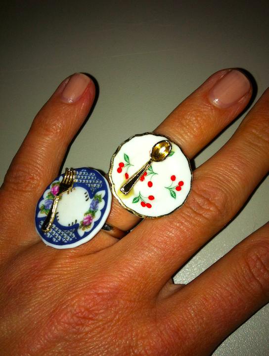 Foto einer Hand mit zwei Fingerringen, die mit kleinen Tellern und Besteck dekoriert sind.
