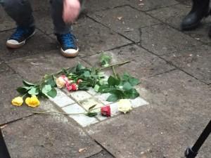 Blumen liegen auf den frisch verlegten Stolperstein von Elli Smula