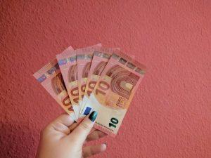 Eine Hand hält fünf 10€-Scheine vor einer roten Wand.
