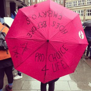 """Pnkfarbener aufgespannter Regenschirm, auf dem ein Aufkleber mit dem Mädchenmannschaftslogo klebt und auf den folgendes gesxchrieben wurde: """"Hoes before embryos"""", """"pro choice for life"""" und die durchkreuzten Paragrafennummern 218 und 219a"""