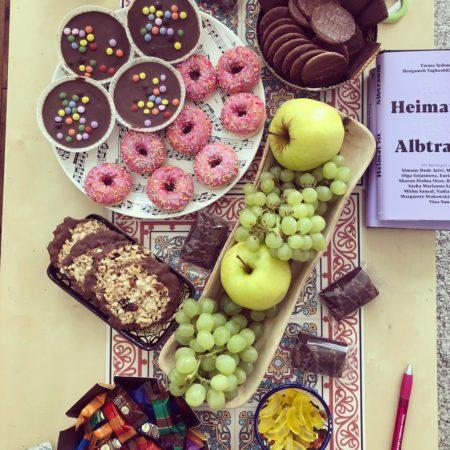 Ein Tisch voller Süßigkeiten, Kekse, Obst und Donuts