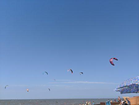 Blauer Himmerl, am unteren Bildrand ist das Meer zu sehen. Im Himmel ein Reihe von bunten Kites.