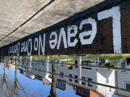 """Foto einer Mauer, auf die mit weißer Farbe in großen Buchstaben der Slogan """"Leave no one behind"""" gemalt wurde"""